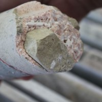 Example of drill core showing a coarse-grained cream-pale green fluorapatite crystal which is about 0.8 in (2 cm) across. The smaller crystals are predominantly zeolite and minor calcite and infill the gaps between the larger fluorapatite crystals - at the Nolans Bore deposit, Nolans Rare-Earth Project, Northern Territory, Australia.